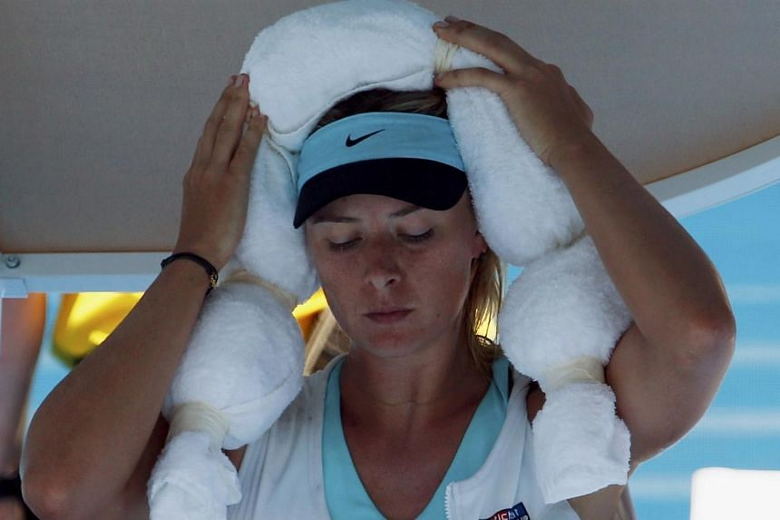 Maria Sharapova of Russia holds an ice-packed towel to her head while wearing an ice vest during a break in play in her women's singles match against Karin Knapp of Italy at the Australian Open 2014 tennis tournament in Melbourne on Thursday, Jan 16,