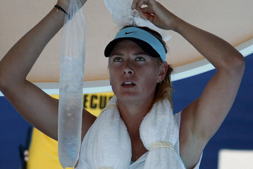 Maria Sharapova of Russia holds ice on her head during her women's singles match against Karin Knapp of Italy at the Australian Open 2014 tennis tournament in Melbourne on Thursday, Jan 16, 2014. -- PHOTO: REUTERS