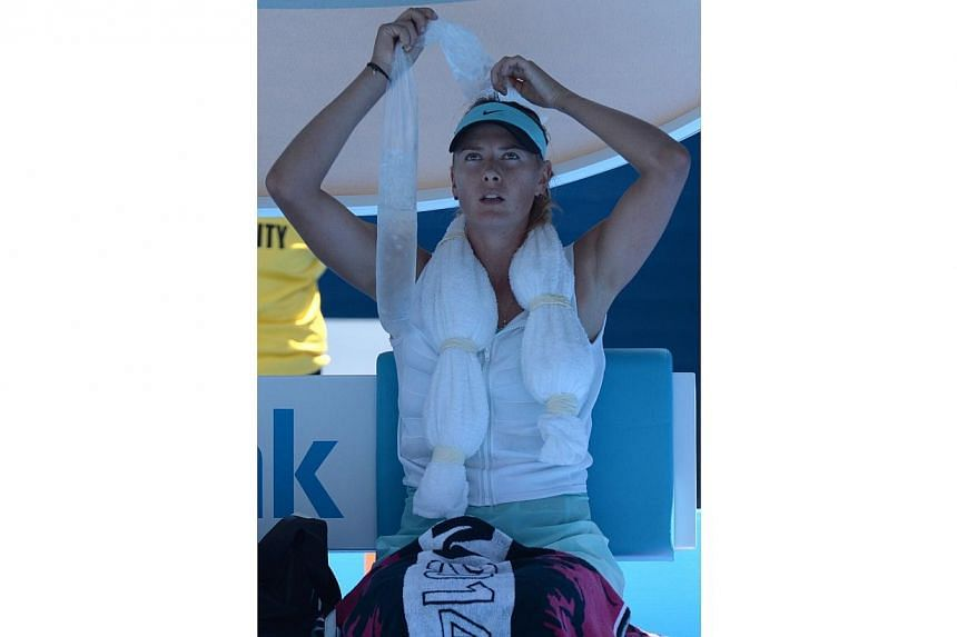 Maria Sharapova of Russia holds ice on her head during her women's singles match against Karin Knapp of Italy at the Australian Open 2014 tennis tournament in Melbourneon Thursday, Jan 16, 2014.-- PHOTO: AFP