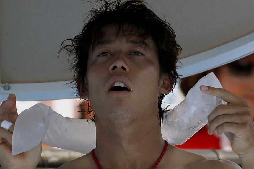 Kei Nishikori of Japan holds an ice pack around his neck during his men's singles match against Dusan Lajovic of Serbia at the Australian Open 2014 tennis tournament in Melbourne on Thursday, Jan 16, 2014. -- PHOTO: REUTERS