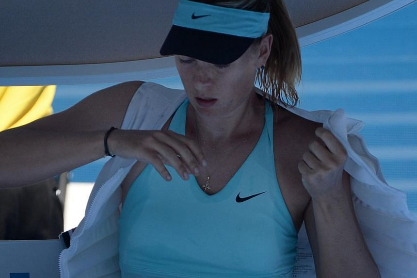 Maria Sharapova of Russia puts on an ice vest during a break in play in her women's singles match against Karin Knapp of Italy at the Australian Open 2014 tennis tournament in Melbourneon Thursday, Jan 16, 2014.-- PHOTO: AFP