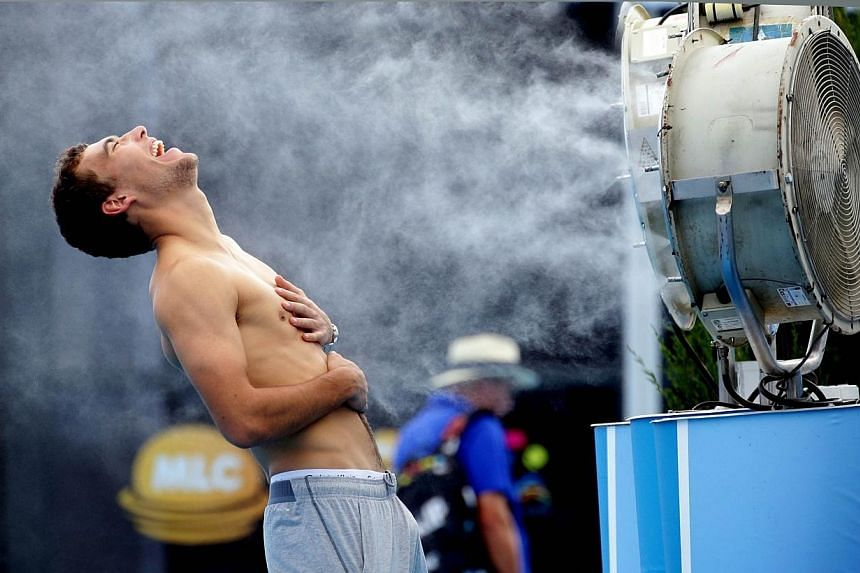 Jerzy Janowicz of Poland poses beside a water fan on The Grand Slam Oval on day four of the 2014 Australian Open tennis tournament in Melbourne on Thursday, Jan 16, 2014. -- PHOTO: AFP