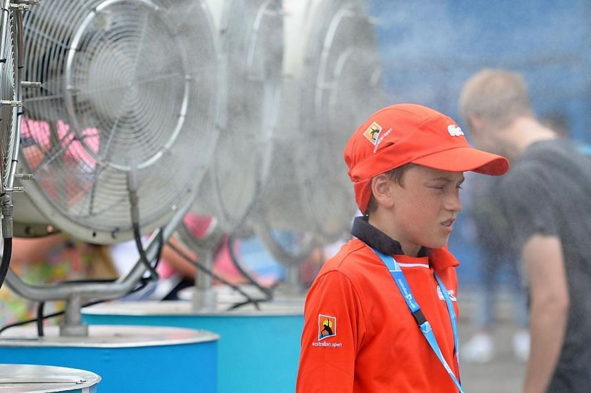 A ball boy cools off with fans and mist put out for spectators as a heat wave continues to sizzle on day three of the 2014 Australian Open tennis tournament in Melbourne on Jan 15, 2014. -- PHOTO: AFP