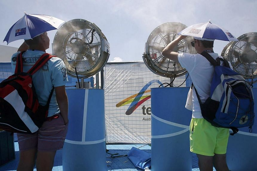 Spectators cool off in front of a misting fan at the Australian Open 2014 tennis tournament in Melbourne, Jan 15, 2014. -- PHOTO: REUTERS
