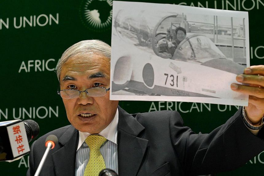 Mr Xie Xiaoyan, China's Ambassador to Ethiopia and permanent Representative to the African Union, holds up a photo showing Japanese Prime Minister Shinzo Abe in a fighter jet during a press conference on Japanese and Chinese relations at the Africa
