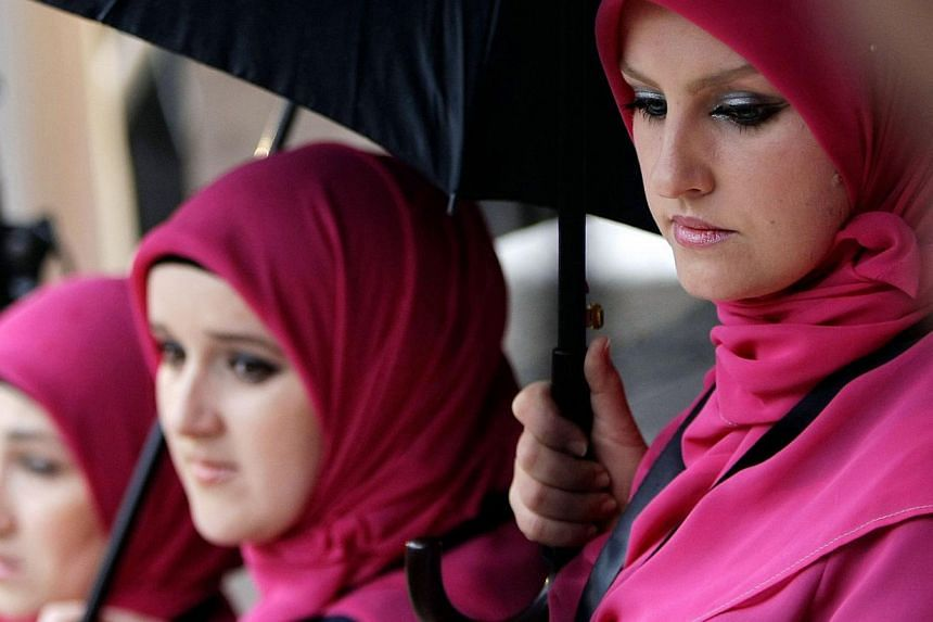Bosnian Muslim women take cover from the rain under umbrellas during the re-opening ceremony of the Gazi Husrev-bey library in Sarajevo, on Jan 15, 2014. -- PHOTO: AFP