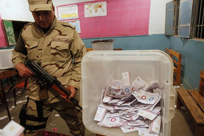 An Egyptian army soldier stands guard as officials count ballots after polls closed during the final stage of a referendum on Egypt's new constitution at the constitutional referendum commission in Cairo, on Jan 15, 2014.Egyptians who voted in