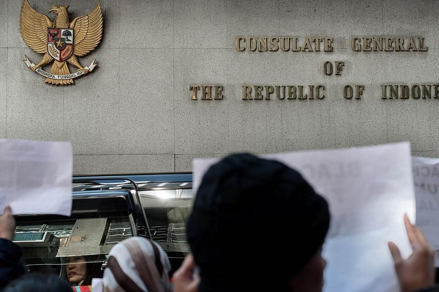 A woman sitting in a passing car (left) looks at maids and rights activists protesting in front of the Indonesian consulate over allegations of an Indonesian maid being abused in Hong Kong, on Jan 16, 2014. -- PHOTO: AFP