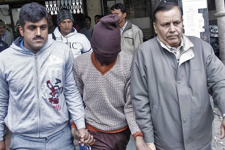 Plain-clothes police escort men (face covered) accused of a gang rape outside a court in New Delhi, on Jan 16, 2014. Indian police carried out raids across New Delhi Thursday, Jan 16, 2014, as they hunted for a further five men wanted over the gang-r