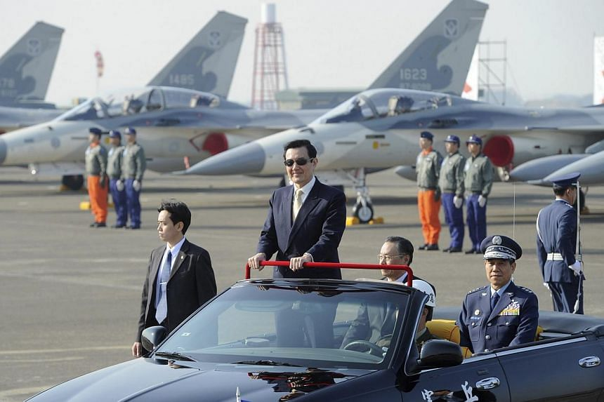 Taiwan's President Ma Ying-jeou stands in a car as he inspects an air base with Air Force Indigenous Defence Fighter (IDF) jets nearby during a ceremony to mark the upgrade of the IDF's weapon system in Tainan, on Jan 16, 2014. -- PHOTO: REUTERS