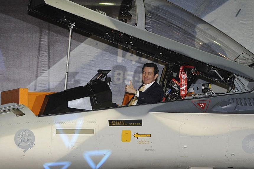 Taiwan's President Ma Ying-jeou gestures as he sits in a Taiwan Air Force Indigenous Defence Fighter (IDF) jet with an upgraded weapon system during a ceremony at an air base in Tainan, on Jan 16, 2014. -- PHOTO: REUTERS