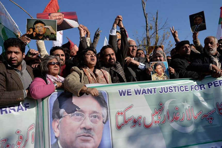 Pakistani supporters of former military ruler Pervez Musharraf carry posters bearing his image and shout slogans during a rally in Islamabad on January 15, 2014. -- PHOTO: AFP