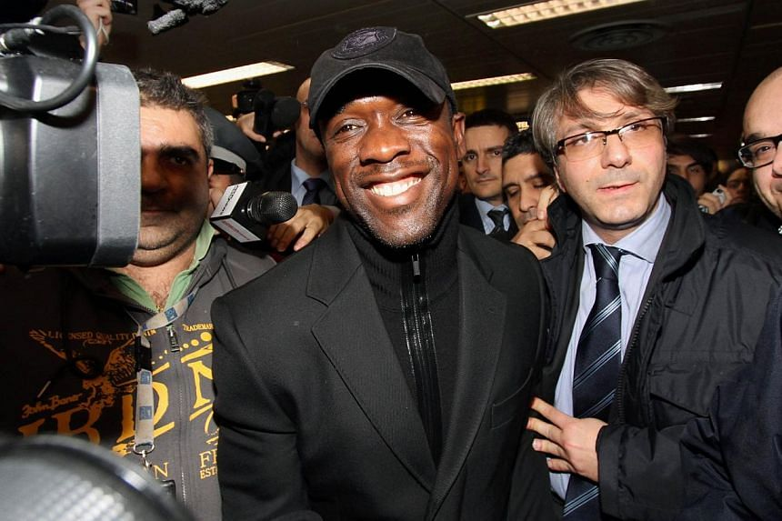 """Former Dutch football player and new AC Milan coach Clarence Seedorf (centre) smiles upon his arrival at Linate airport in Milan on Jan 15, 2014.Seedorf said there is """"a lot to do"""" if he is to hoist AC Milan back to the heights of European and"""
