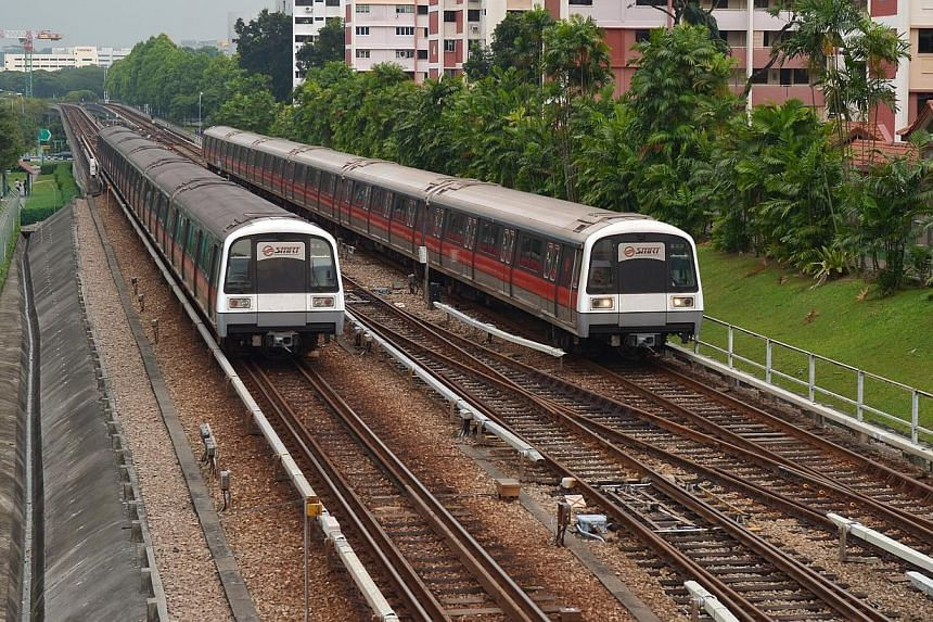 Two MRT trains travelling on the tracks along Ang Mo Kio Avenue 8.Low-wage workers and disabled individuals will soon get help with their public transport fares.-- ST FILE PHOTO:ALPHONSUS CHERN