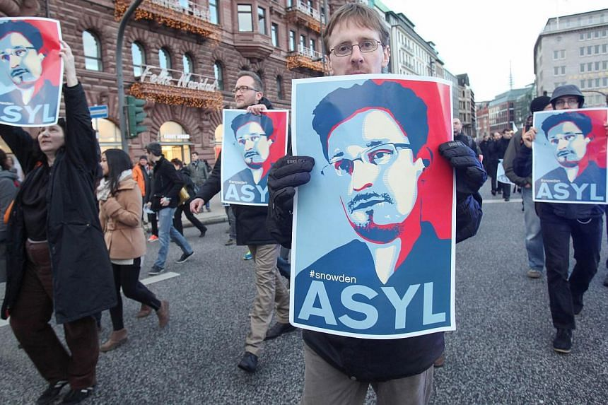Protesters in Hamburg, Germany, marching in support of asylum for former NSA contractor Edward Snowden on Dec 28, 2013. After months of gushing intelligence leaks and warnings the US national security state has gone rogue, President Barack Obama will