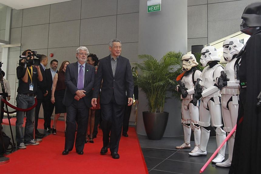 Singapore Prime Minister Lee Hsien Loong (centre, right), accompanied by filmmaker George Lucas, is greeted by people in Darth Vader and Storm Trooper costumes at the official opening of the Sandcrawler Building on Jan 16, 2014. -- ST PHOTO: KEVIN LI