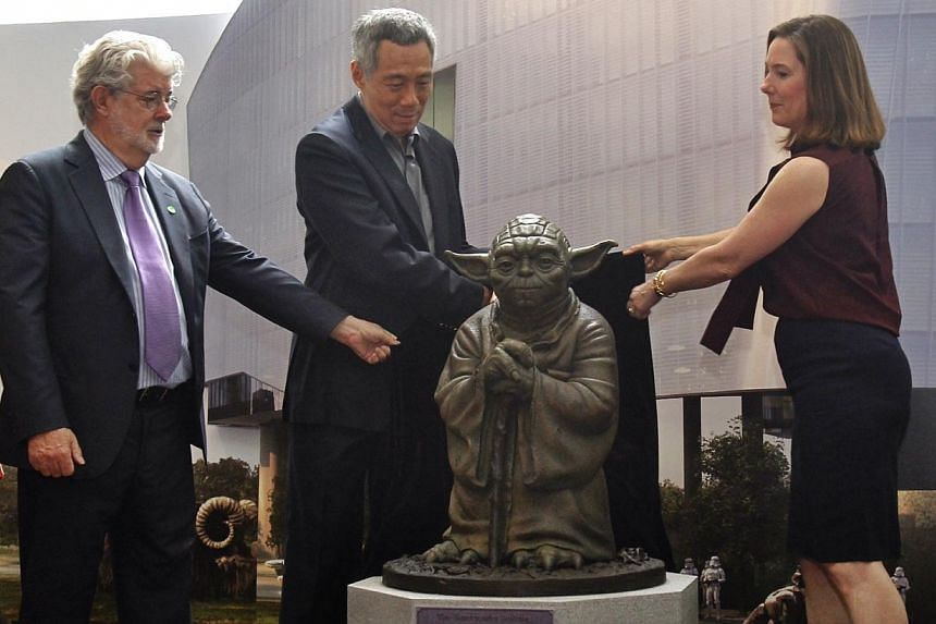 Prime Minister Lee Hsien Loong (centre) joined by Kathleen Kennedy (right), President of Lucasfilm, and Mr George Lucas in the unveiling of Yoda during the official opening for Sandcrawler building on Jan 16, 2014. -- ST PHOTO: KEVIN LIM