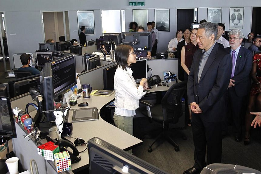 Ms Long Yinghan, a local talent and digital artist, describes her work to Prime Minister Lee Hsien Loong during his tour of the Sandcrawler building on Jan 16, 2014. -- ST PHOTO: KEVIN LIM