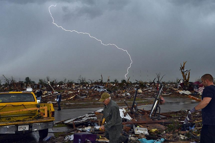 Lightning strikes during a thunder storm as tornado survivors search for salvagable stuffs at their devastated home on May 23, 2013, in Moore, Oklahoma. Seven weather disasters, including tornadoes, droughts and a flood, cost the United States (US) a