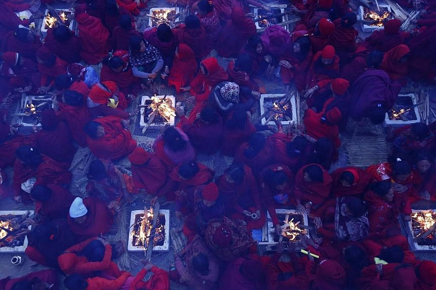Hindu women sit around fires to warm themselves up before taking a holy bath at Saali River during the first day of the Swasthani Brata Katha festival at Sankhu in Kathmandu on Jan 16, 2014. See more pictures from around the world in Through The