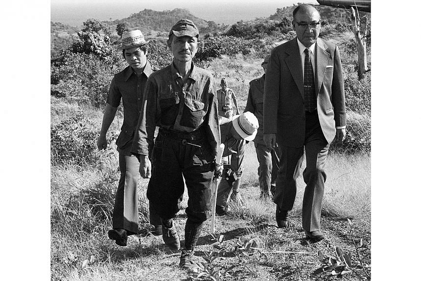 This picture taken on March 11, 1974, shows former Japanese imperial army soldier Hiroo Onoda (second left) walking from the jungle where he had hidden since World War II, on Lubang island in the Philippines. Mr Onoda has died in Tokyo at the age of