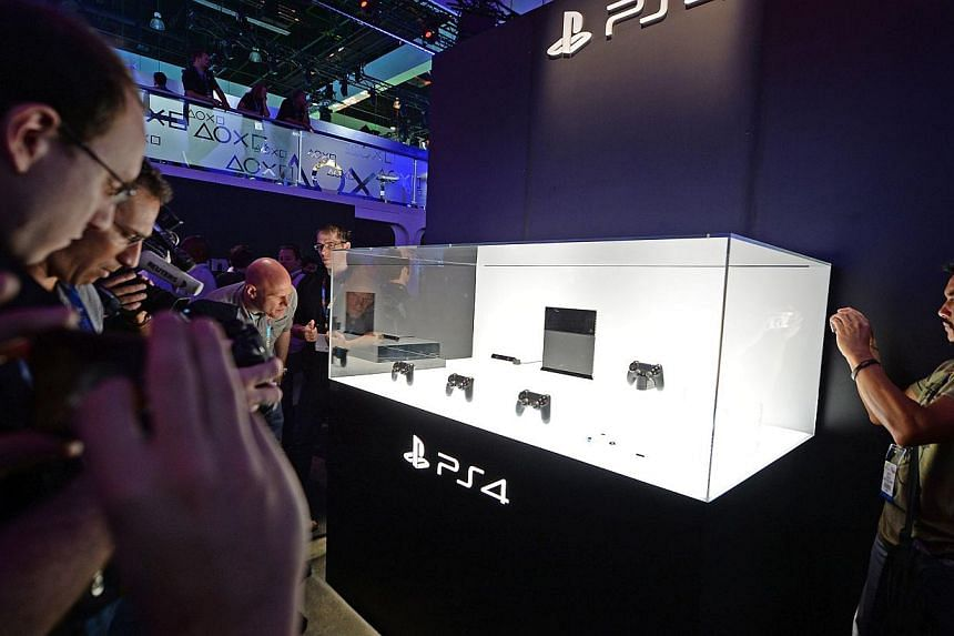 Attendees photograph the new Sony PlayStation 4 (PS4) console on the first day of the Electronic Entertainment Expo (E3) in Los Angeles, California, on June 11, 2013. NPD Group reported on Thursday, Jan 17, 2014 that new consoles from Sony and
