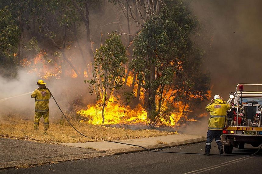 This handout photo taken on Jan12, 2014 and supplied by Australia's Department of Fire and Emergency Services (DFES) shows firefighters working to contain wildfires a suburb east of Perth in the state of Western Australia. One person has died in a ma