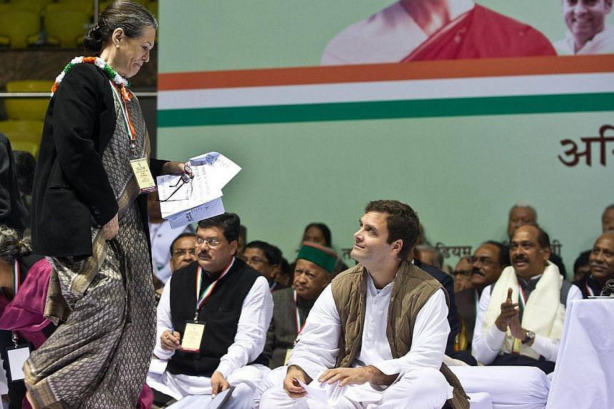 Indian Congress Party Vice President Rahul Gandhi (C) smiles as Congress Party president, his mother Sonia Gandhi, arrives during the All-India Congress Committee meeting in New Delhi on January 17, 2014. India's ruling party was set to put on a unit