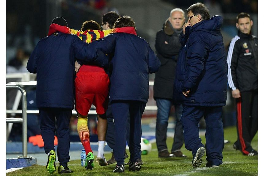 """Barcelona's Argentinian coach Gerardo """"Tata"""" Martino (right) looks on as Barcelona's Brazilian forward Neymar da Silva Santos (second left) is assisted off the field during the Spanish Copa del Rey (King's Cup) round of 16 second-leg football match G"""