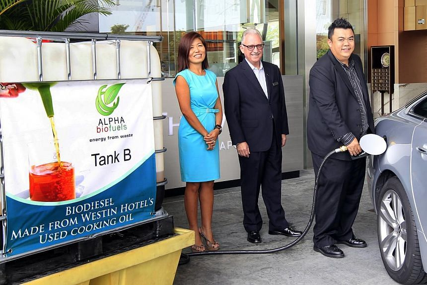 Allan Lim, CEO of Alpha Biofuels, pumping biodiesel into the car.A five-star hotel's limousines are running on used cooking oil from its own kitchen, thanks to a local company's machine that produces biodiesel for luxury cars. -- ST PHOTO:&nbsp