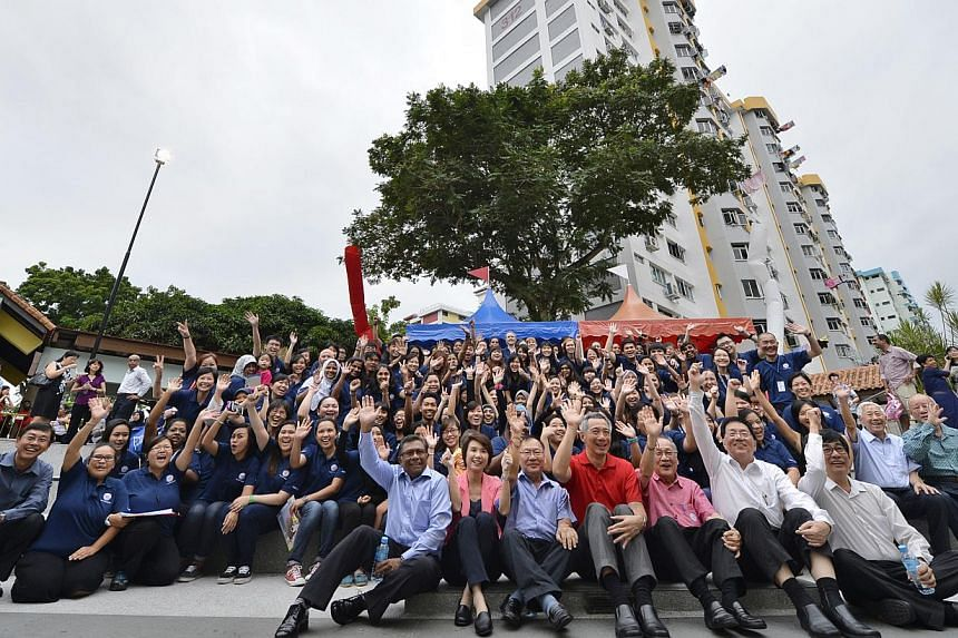 Prime Minister Lee Hsien Loong taking time off to have a group photo with staff of Thye Hua Kwan Early Intervention Programme for Infants and Children Centre staff and invited guests at the amphitheatre next to Block 313 in Ang Mo Kio. The Gover