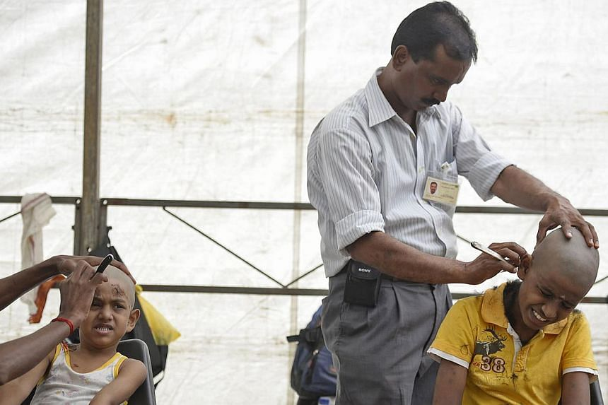 (From left to right) Enthressan Shanmugam, 4, and nine-year-old Samiyappa Yuvarajan react as they have their hair shorn at Sri Thendayuthapani Temple at Tank Road during this year's Thaipusam festival on Jan 17, 2014. Hindu devotees have their heads