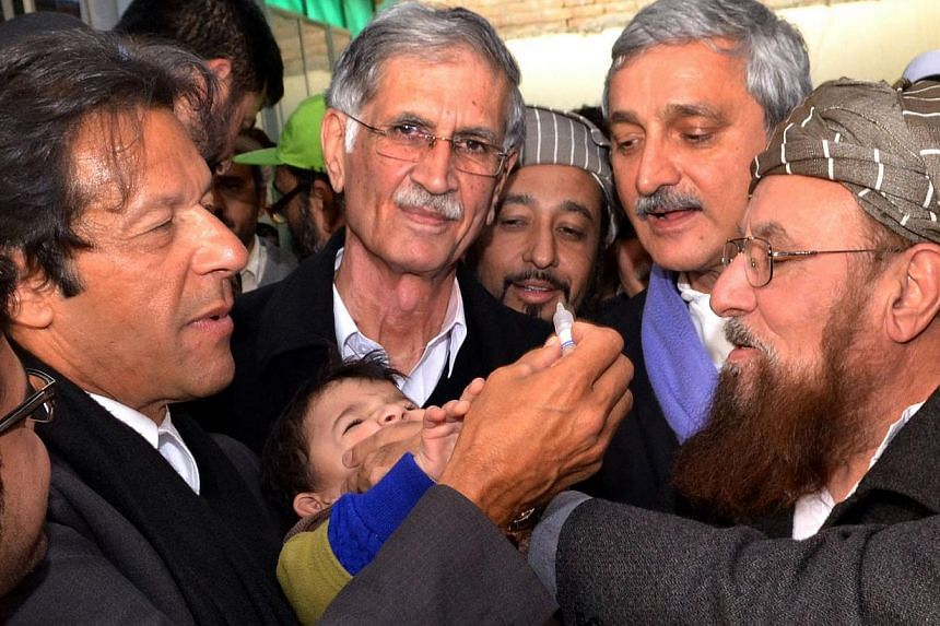 In this handout photograph released authorities of the northwestern Khyber Pakhtunkhwa province, Pakistani cricketer-turned-politician Imran Khan (L) gives polio vaccine drops to a young child in the town of Akoda Khattak, 50 kms east of Peshawar. Mr