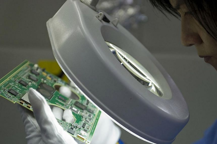 A worker inspects a printed circuit board on the assembly line at the Venture Corp factory in Singapore. Singapore's non-oil domestic exports were up 6 per cent in December from a year ago, due to an increase in shipments of non-electronic products.