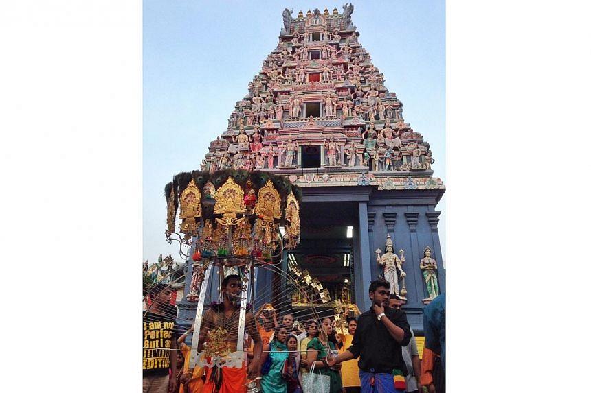 Devotees walk out of Sri Srinivasa Perumal Temple carrying kavadis at this year's Thaipusam festival. -- ST PHOTO: MUGILAN RAJASEGERAN