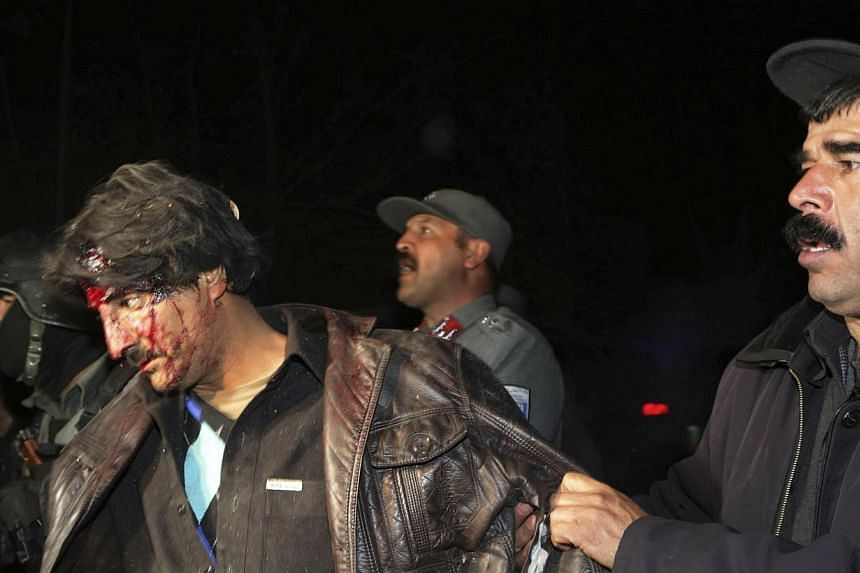 Afghan policemen help an injured man at the site of an explosion in Kabul on Jan 17, 2014.A total of 21 people, including 13 foreigners, died in a Taleban suicide assault on a popular restaurant in Kabul, police said on Saturday, with two Briti