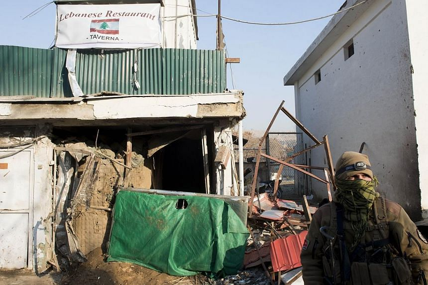 An Afghan special force soldier stands guard next to the damaged entrance of a Lebanese restaurant that was attacked in Kabul,on Jan 18, 2014. -- PHOTO: AFP