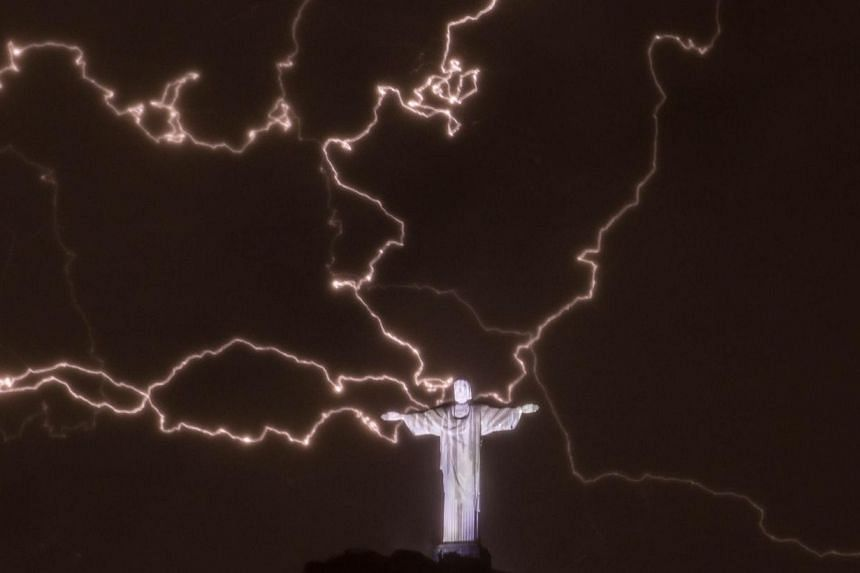 Lightning flashes over the statue of Christ the Redeemer on top of the Corcovado hill in Rio de Janeiro, Brazil, on Jan 16, 2014. The iconic statue of Jesus has lost a thumb tip to lightning, a report said on Friday. -- FILE PHOTO: AFP