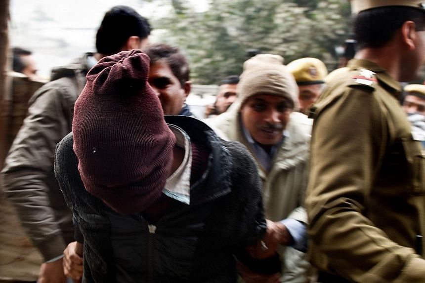 Indian policemen escort a suspect in the gang-rape of a Danish tourist at the Tis Hazari Courts in New Delhi on Jan 16, 2014. Three more male suspects were arrested Friday over the gang-rape of a Danish tourist that has renewed the spotlight on