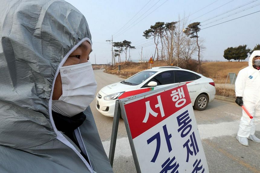 South Korean quarantine officials man a checkpoint near a poultry farm, where a case of avian influenza was reported, in Gochang in North Jeolla Province, some 300km south-west of Seoul, on Jan 17, 2014. -- PHOTO: AFP