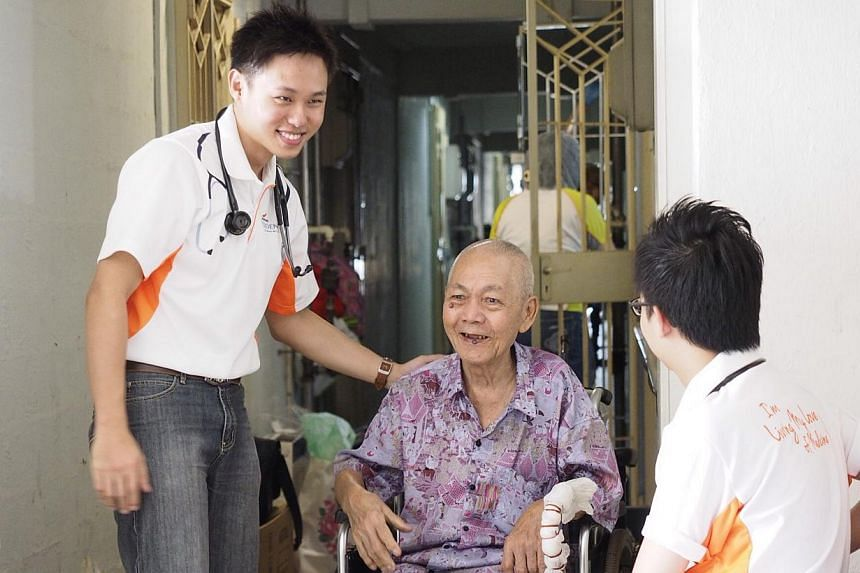 Residents from SGH, Dr Eugene Wong and Dr Andrew Mok provide health screening and speak with Mr Wong Kwan Cheok, a beneficiary of SGH's annual Project GroomOver on Jan 18, 2014. . -- PHOTO: SGH