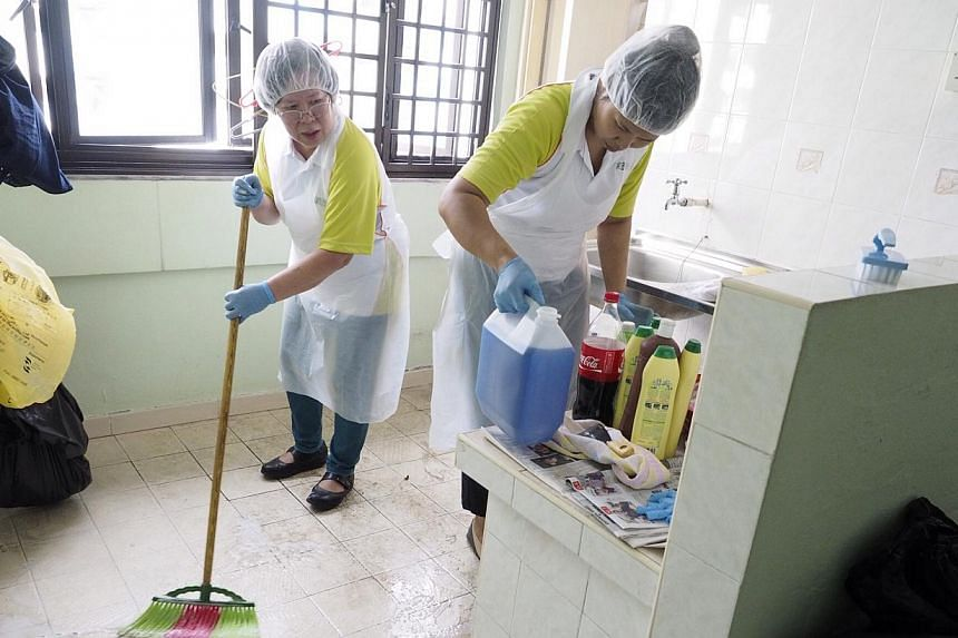 Volunteers Suriani Zahari and Anne Tok Kim Lian clean the kitchen of a needy and elderly resident for SGH's annual project GroomOver on Jan 18, 2014. -- PHOTO: SGH