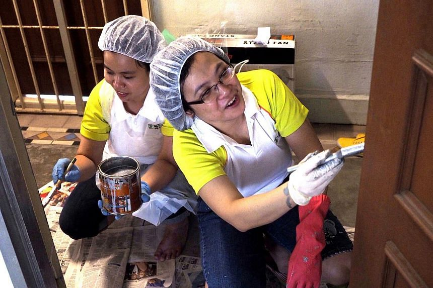 Volunteers Tan Sin Yain and Ronalyn Cruz paint the home of an elderly beneficiary for SGH's annual Project GroomOver on Jan 18, 2014. -- PHOTO: SGH