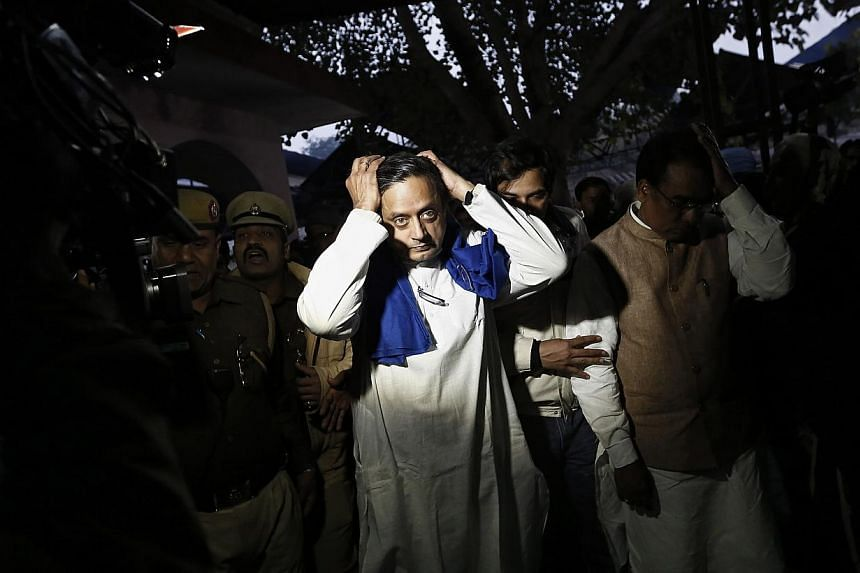 """India's junior human resource development minister Shashi Tharoor (C) gestures after performing the last rites for his wife Sunanda Puskhar at a cremation ground in New Delhi on Jan 18, 2014. The death of Sunanda was described as """"sudden"""" and """"unnatu"""
