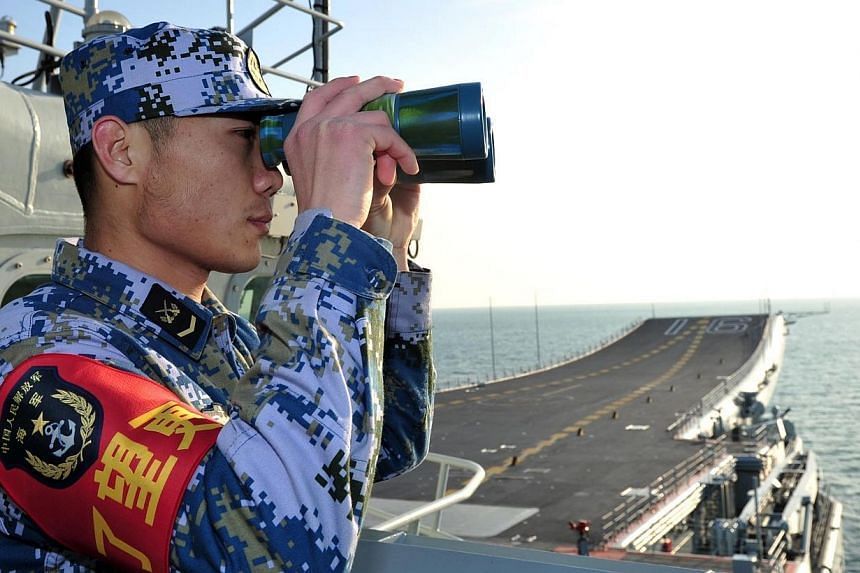 A naval soldier of the Chinese People's Liberation Army (PLA) views through a pair of binoculars onboard China's first aircraft carrier Liaoning as it visits a military harbour on the South China Sea in Sanya, Hainan province, in this undated picture