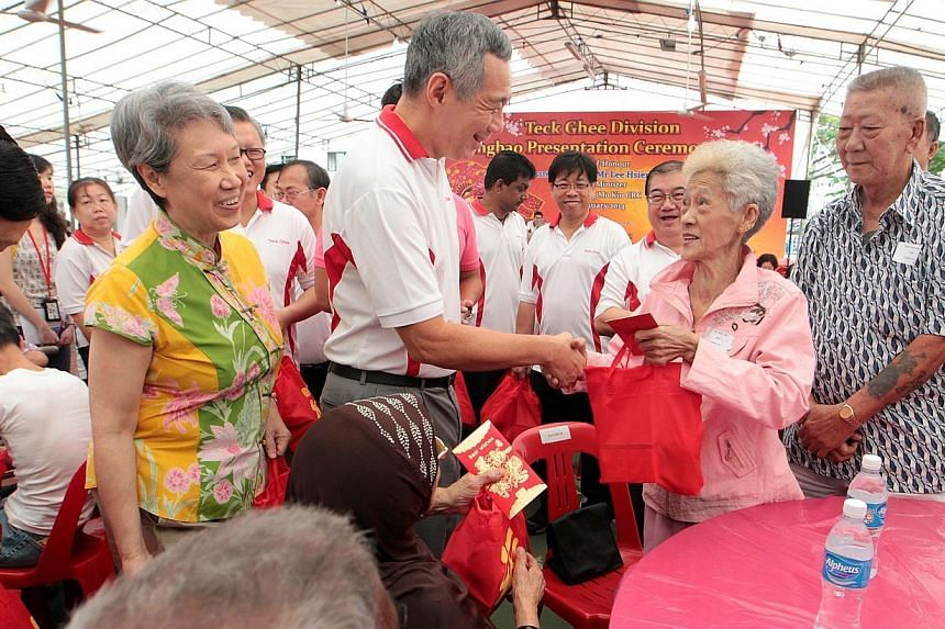 Prime Minister Lee Hsien Loong (centre), with his wife Ho Ching (in yellow), hands out a hongbao and goodie bag to one of the 382 needy residents in the Teck Ghee Division who received hongbaos at the Teck Ghee Division Hongbao Presentation Ceremony