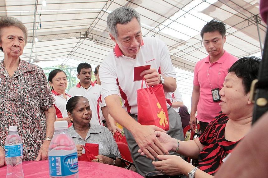 Prime Minister Lee Hsien Loong (third from right) hands out a hongbao and goodie bag to Madam Kok Lai Wu (extreme right), 64, one of the 382 needy residents in the Teck Ghee Division who received hongbaos at the Teck Ghee Division Hongbao Presentatio