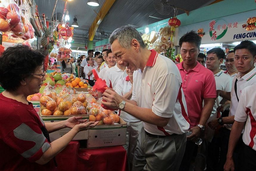Prime Minister Lee Hsien Loong (centre) returns a pair of mandarin oranges as a form of Chinese New Year greeting to a fruits seller as he goes on a walkabout after handing out hongbaos to 382 needy residents at the Teck Ghee Division Hongbao Present