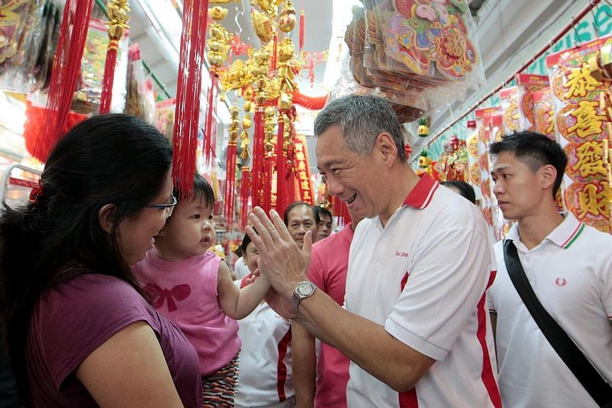 Prime Minister Lee Hsien Loong (second from right) gets a high five greeting from one-and-half-year-old Chloe Loh (second from left) with her mother Madam Elaine Yee (extreme left), as he goes on a walkabout in the area after handing out hongbaos to