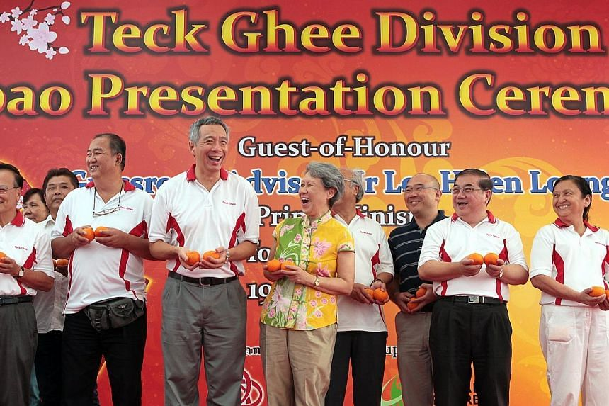 Prime Minister Lee Hsien Loong (third from left) and wife Ho Ching (fourth from left) react on stage after greeting Teck Ghee Division residents with grassroots members.He was attending the Teck Ghee Division Hongbao Presentation Ceremony 2014